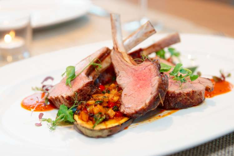 Grilled rack of lamb with vegetables on plate